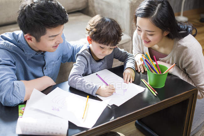 Asian parents helping son with homework — Stock Photo