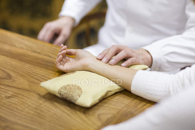 Chinese doctor taking pulse of female patient — Stock Photo