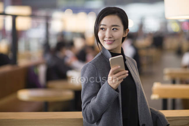 Asian woman holding smartphone in airport — Stock Photo