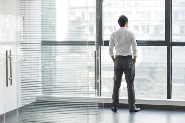 Businessman looking through window, rear view — Stock Photo