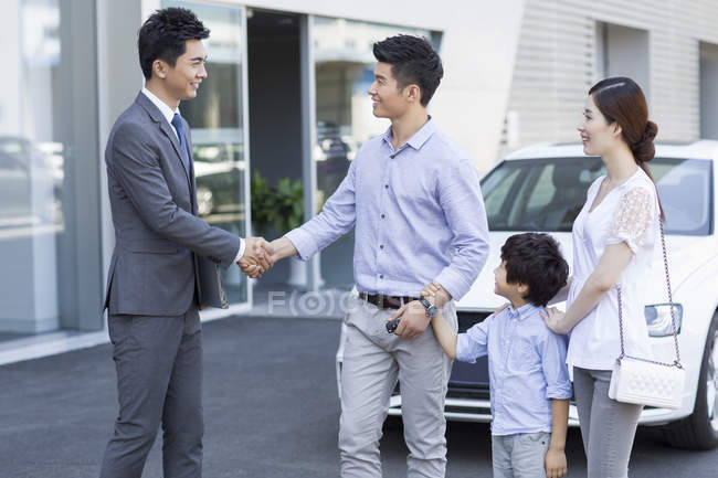 Chinese family shaking hands with car seller in front of showroom — Stock Photo