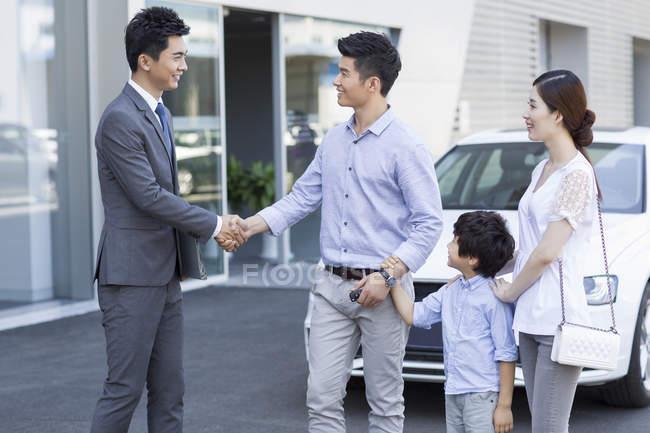 Китайські родини, потискує руку автомобіль продавець перед виставковий зал — стокове фото