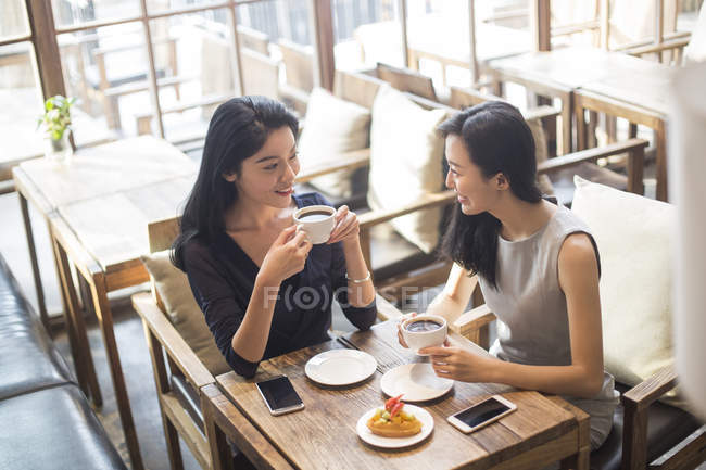 Chinas amigas tomando café y hablando en la cafetería - foto de stock