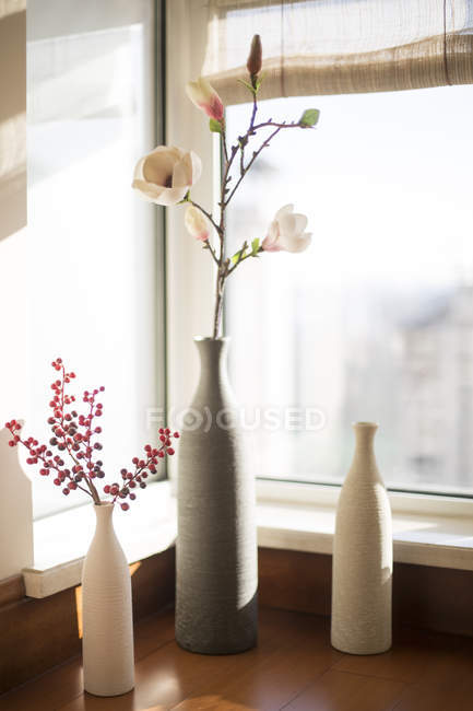 Vases with flowers on window sill — Stock Photo