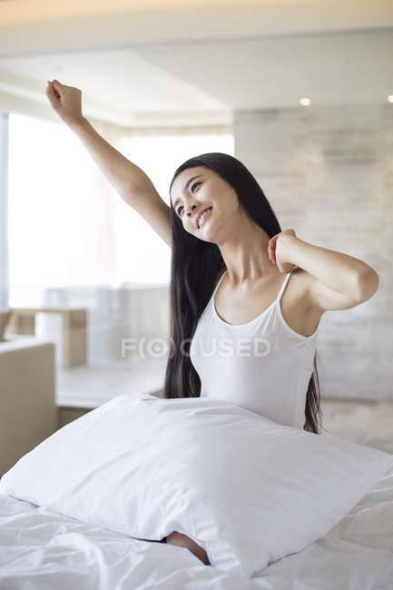 Chinesische Frau Morgen im Bett Strecken und lächelnd — Stockfoto
