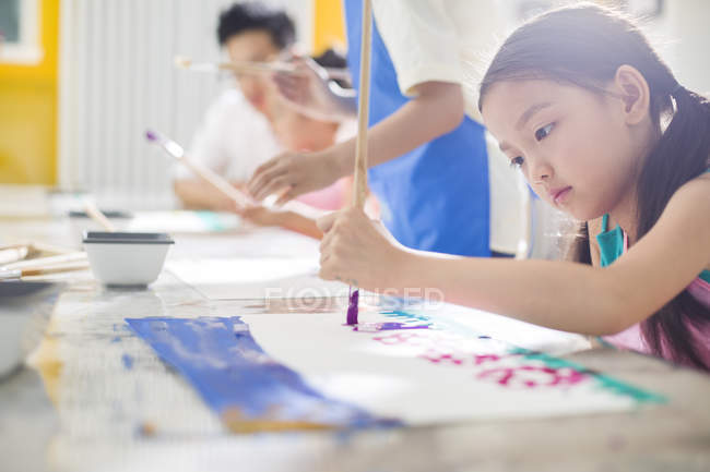 Chinese girl painting in art class with teacher — Stock Photo