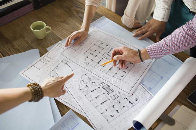 Architetti che lavorano su cianografie al tavolo dell'ufficio — Foto stock