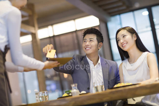 Chinese man paying bill with credit card in restaurant — Stock Photo