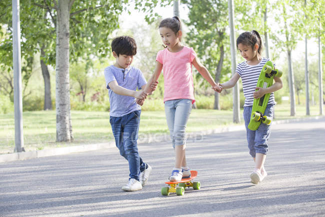 Chinese children skateboarding on park road — Stock Photo