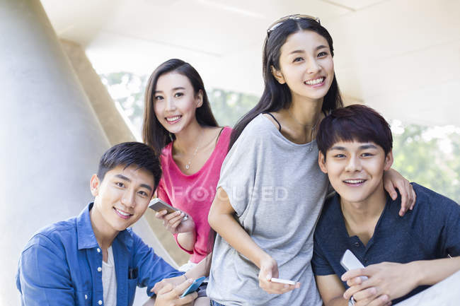 Chinese friends with smartphones looking in camera — Stock Photo