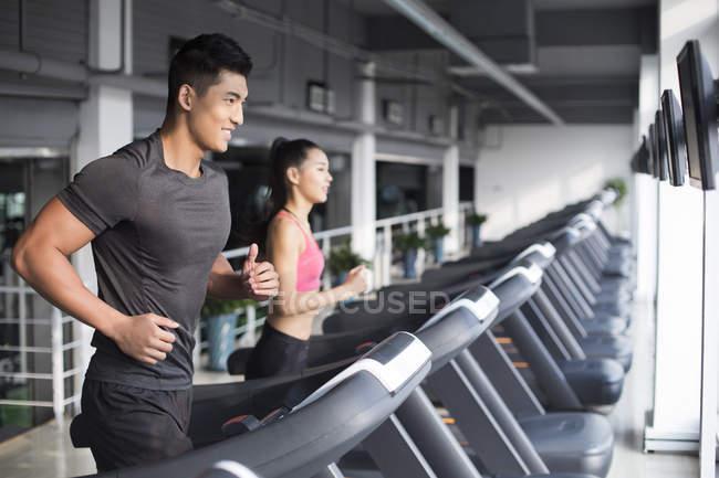 Китайская пара бегает на беговых дорожках в спортзале — стоковое фото