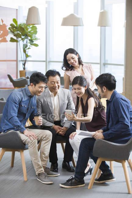 Деловая женщина из Китая показывает смартфон коллегам — стоковое фото