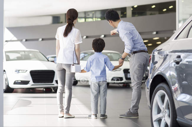 Chinese family in car dealership showroom pointing on cars — Stock Photo