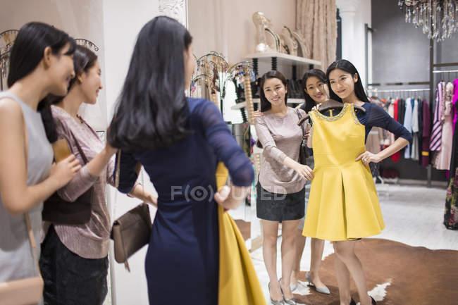Китайские подруги примеряют одежду в магазине одежды — стоковое фото