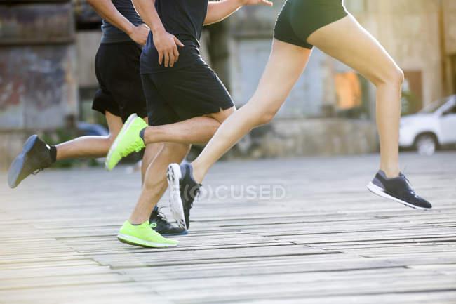 Vista recortada de las piernas de los corredores corriendo por la calle - foto de stock