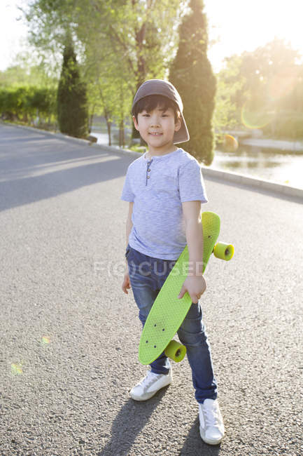 Китайский мальчик позирует со скейтбордом на дороге — стоковое фото