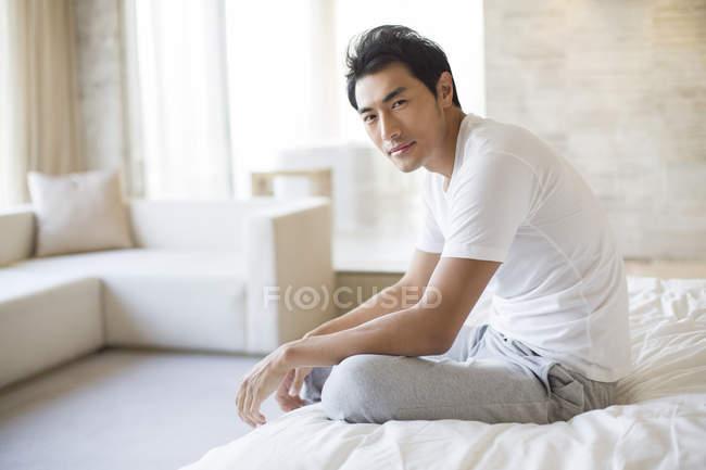 Le Cinesi A Letto.Uomo Cinese Che Si Siede Sul Letto E Guardando A Porte Chiuse In