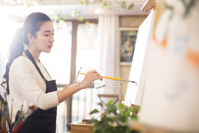 Asian woman painting in art studio — Stock Photo