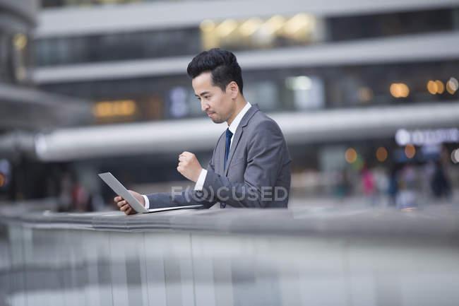 Asiatique homme d'affaires en utilisant ordinateur portable sur la rue — Photo de stock