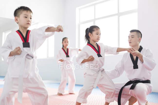 Chinese instructor teaching children Taekwondo — Stock Photo