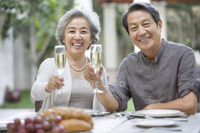 Senior Chinese couple holding champagne flutes at dining table — Stock Photo