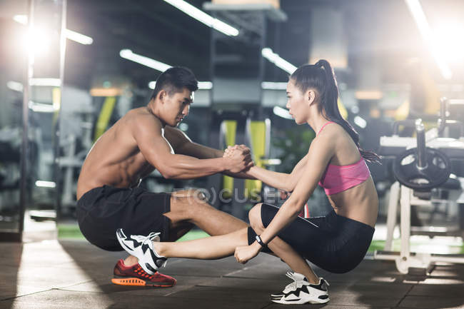 Chinese couple doing sit ups together at gym — Stock Photo
