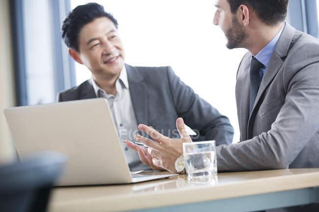 Empresários discutindo trabalharcom com laptop na sala de reuniões — Fotografia de Stock