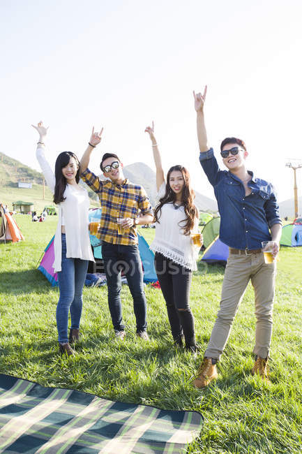 Chinese friends gesturing with beer at music festival camping — Stock Photo