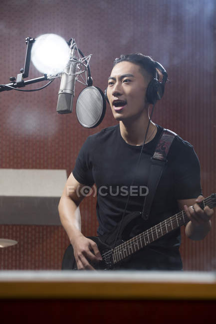 Chinese man singing with guitar in recording studio — Stock Photo