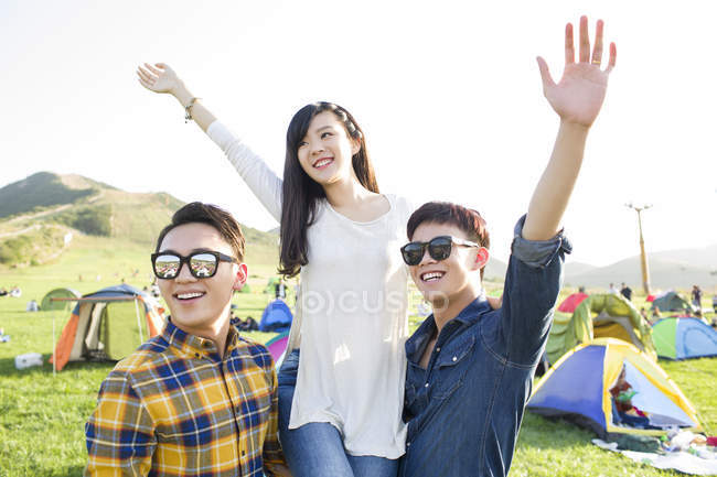 Chinese friends posing with arms raised at festival camping — Stock Photo