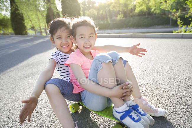 Chinese girls sitting on skateboard — Stock Photo