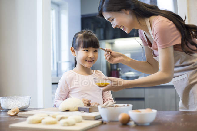 Madre e hija chinas batiendo huevo juntas - foto de stock