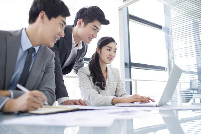 Chinese business people using laptop in meeting room — Stock Photo