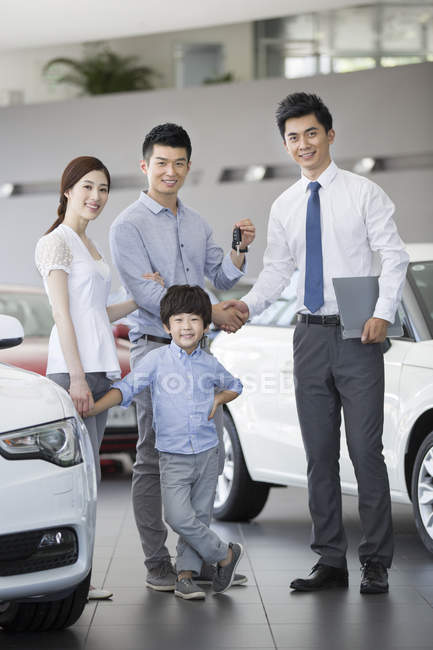 Chinese family with car keys in showroom with car seller — Stock Photo