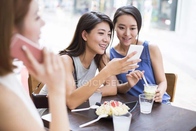 Женщины-подруги используют смартфоны в кафе на тротуаре — стоковое фото