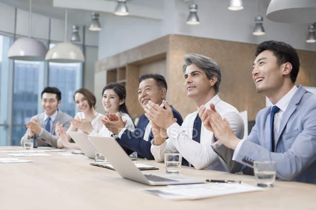 Деловая команда хлопает на заседании в зале заседаний — стоковое фото