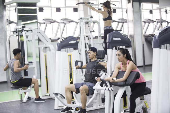 Asian adults using exercise machines at gym — Stock Photo