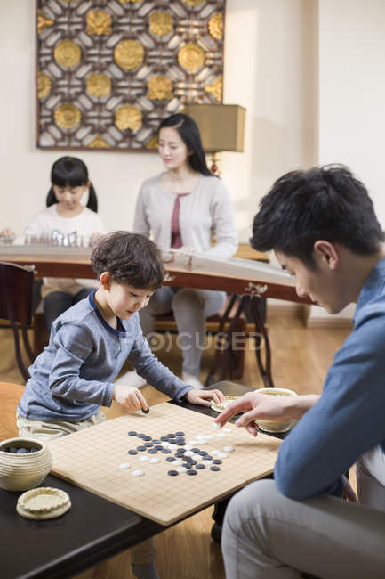 Asian family leisure activities with Go game and musical instrument — Stock Photo