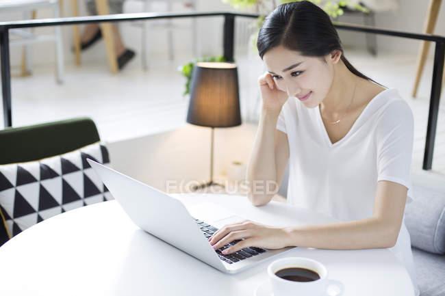 Китайська жінка, використовуючи ноутбук у кафе — стокове фото
