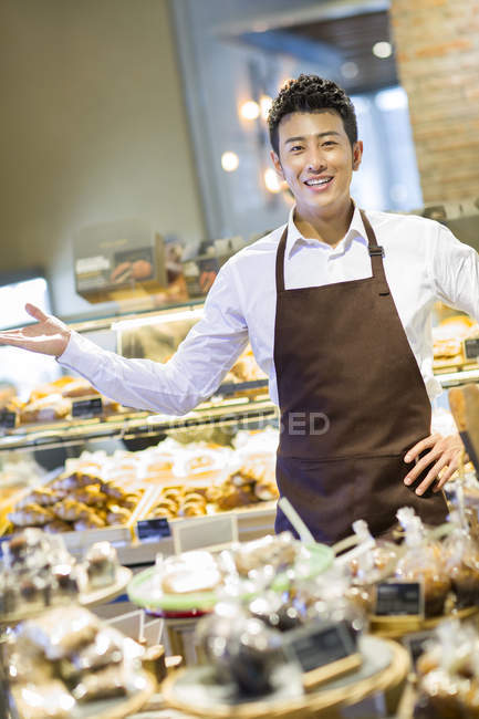 Asian man standing at bakery counter — Stock Photo