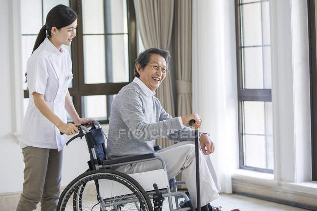 Chinese nursing assistant taking care of senior man in wheelchair — Stock Photo