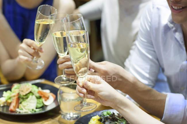 Freunde, die klirrende Gläser beim Abendessen im restaurant — Stockfoto