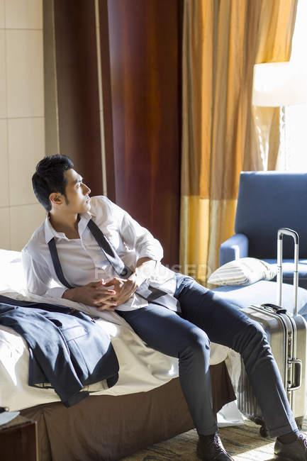 Hombre de negocios chino descansando en la habitación de hotel - foto de stock