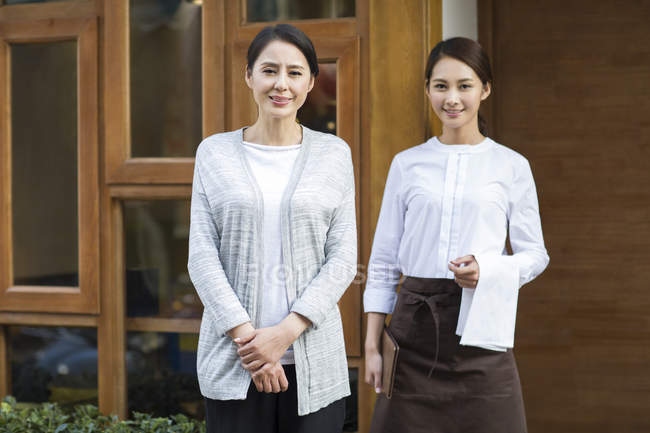 Chinese restaurant owner and waitress standing in doorway — Stock Photo