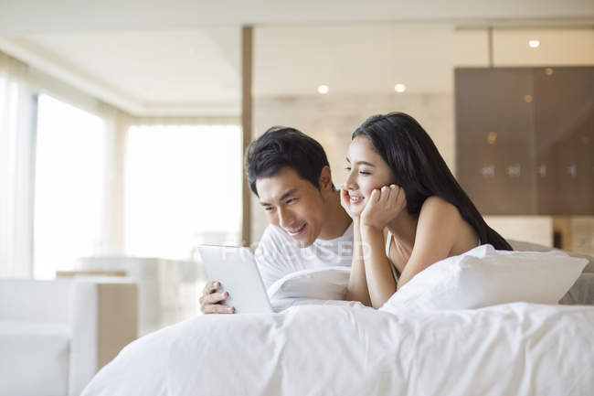 Le Cinesi A Letto.Chinese Couple Using Digital Tablet In Bed Lying Down Wireless