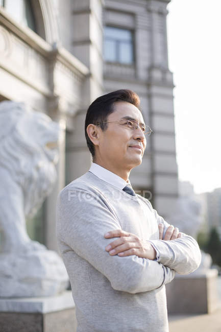 Chinese businessman with arms crossed looking at view in city — Stock Photo