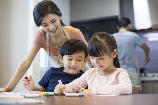 Chinese siblings drawing together at home — Stock Photo