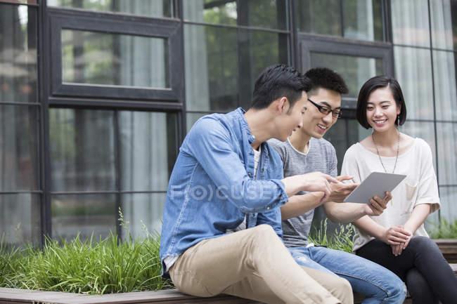 Equipo chino de negocios informal hablando con tableta digital en la ciudad de - foto de stock