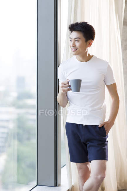 Chinese man holding coffee and looking through window at home — Stock Photo