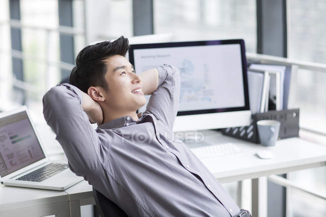 Chinese businessman thinking in office — Stock Photo